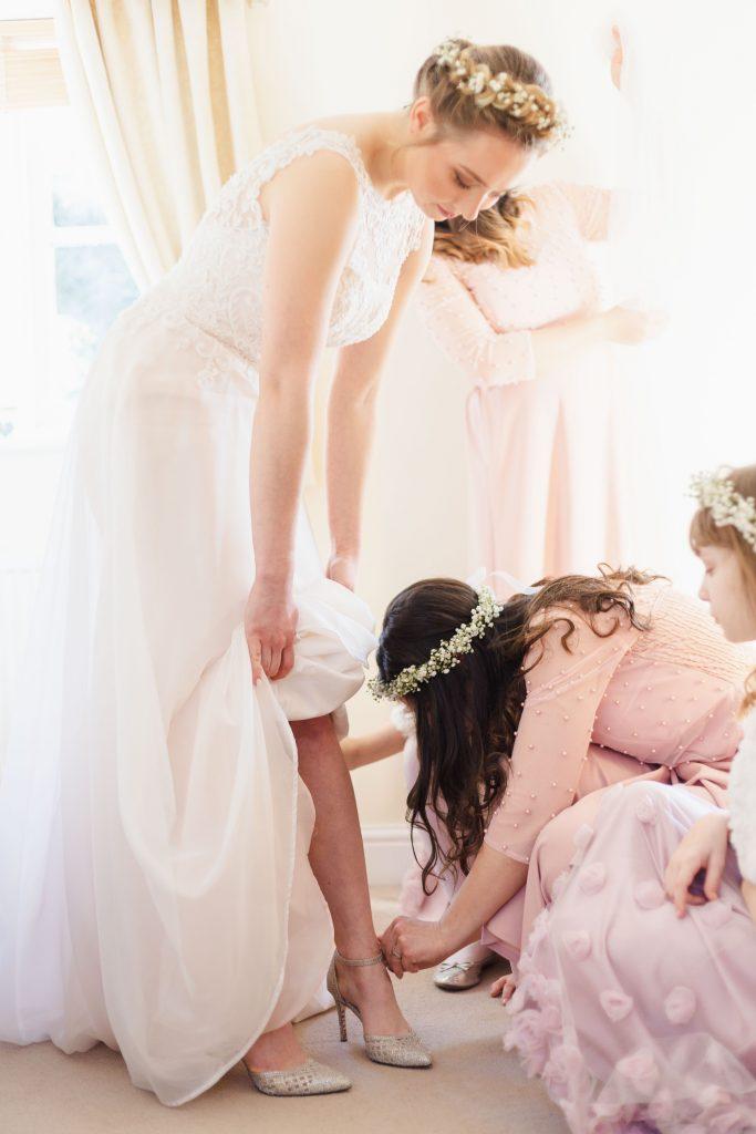 bridesmaid tying up brides shoe