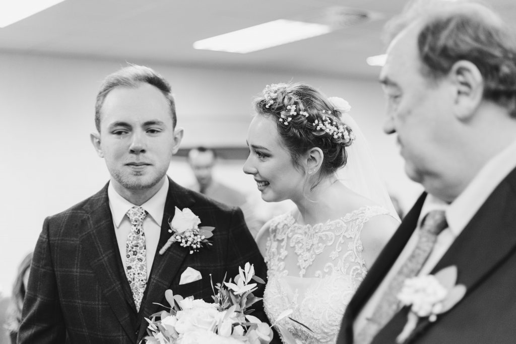 bride comforts emotional groom with father