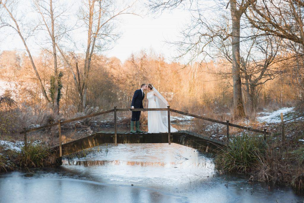 banbury oxfordshire winter wedding couple kissing on a bridge