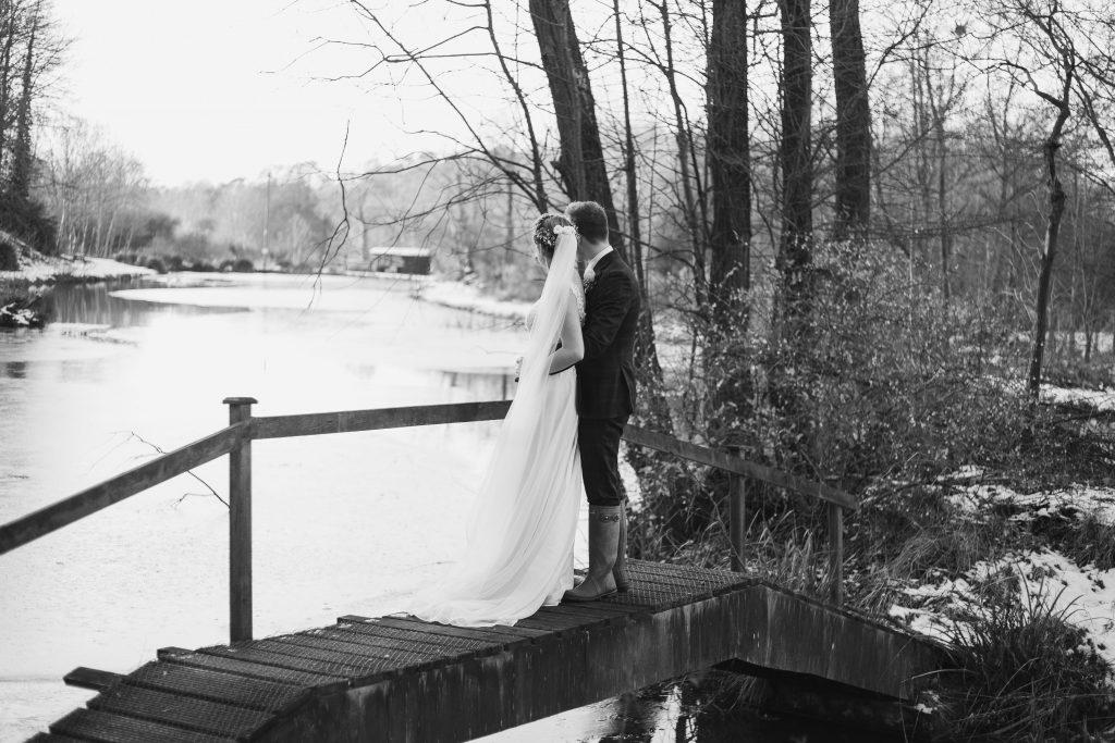 banbury oxfordshire winter wedding standing on bride over lake