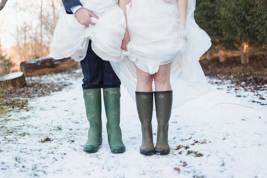 banbury oxfordshire winter wedding couple standing in boots in the snow