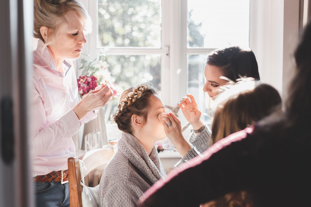 Bride getting her make up done with her mother