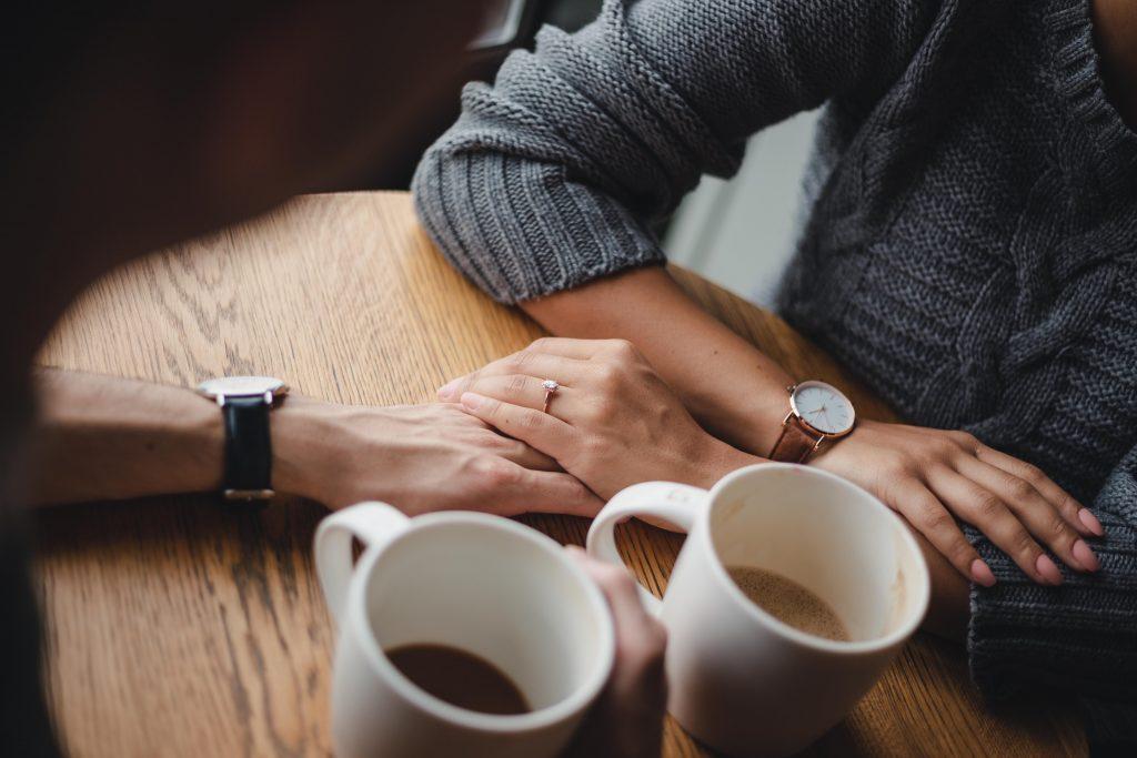 Jodi + Jade holding hands coffee shop