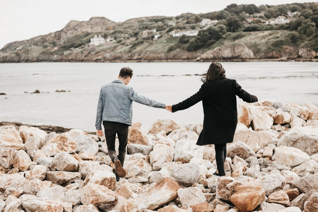 Jodi + Jade Howth engagement shoot couple walking on the rocks