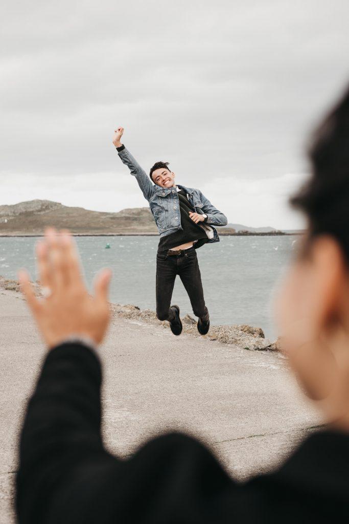 Jodi + Jade Howth engagement shoot fiance jumping for joy engagement ring