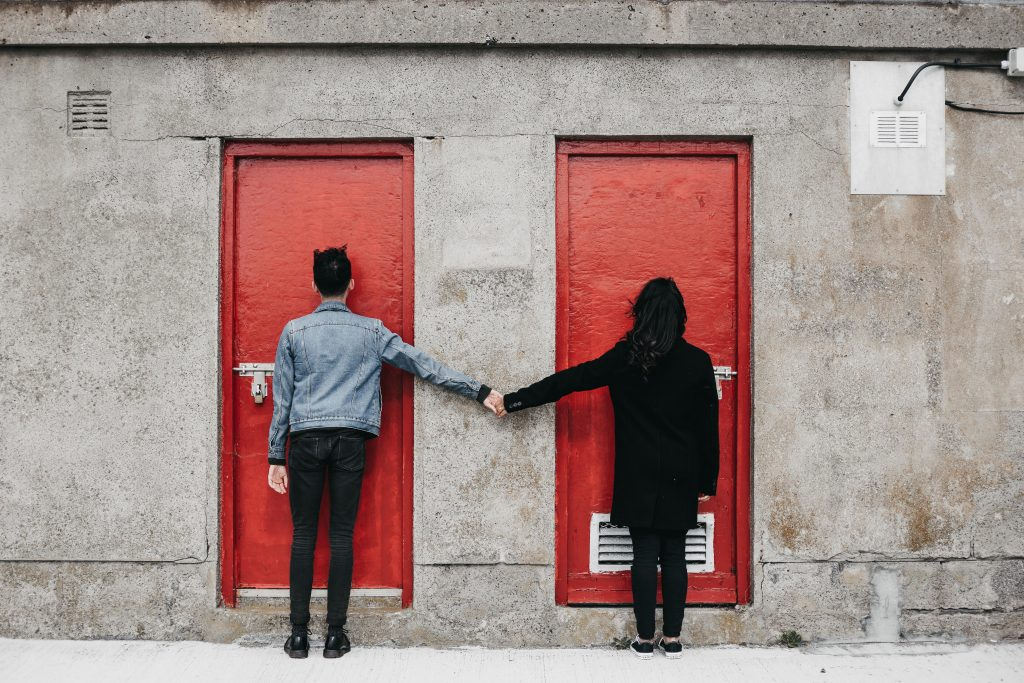 Jodi + Jade Howth engagement shoot couple holding hands looking at a door