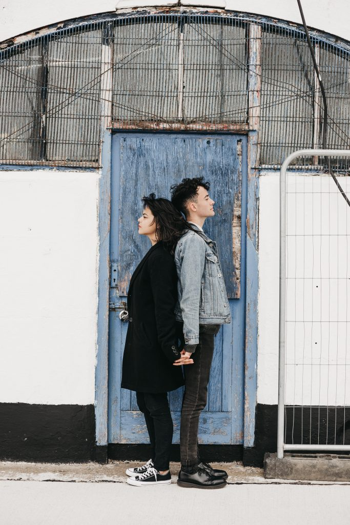 Jodi + Jade Howth engagement shoot standing back to back in front of a blue door