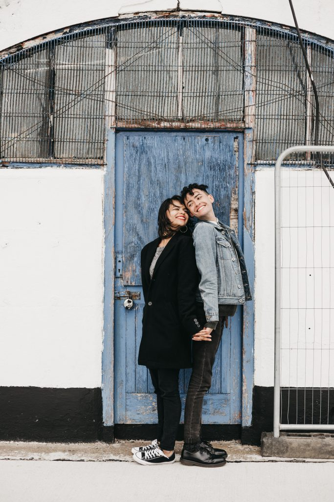 Jodi + Jade Howth engagement shoot looking back at each other in front of a blue door