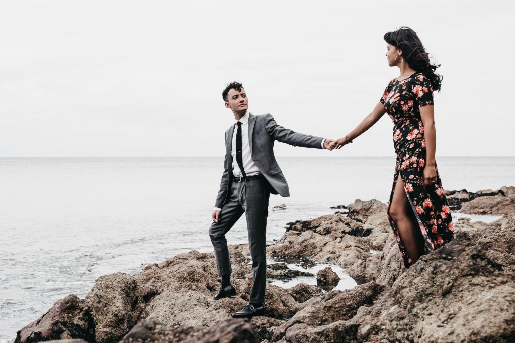 Jodi + Jade Howth engagement shoot posing on the rocks by the ocean
