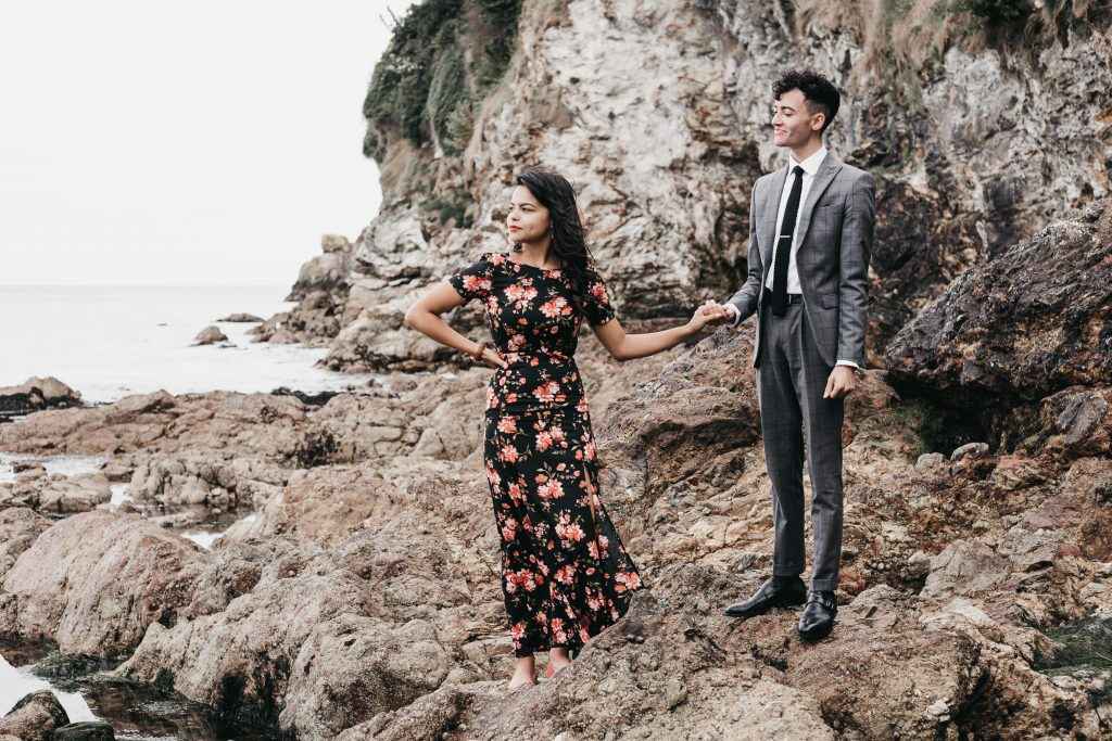 Jodi + Jade Howth engagement shoot holding hands while posing on the rocks by the ocean