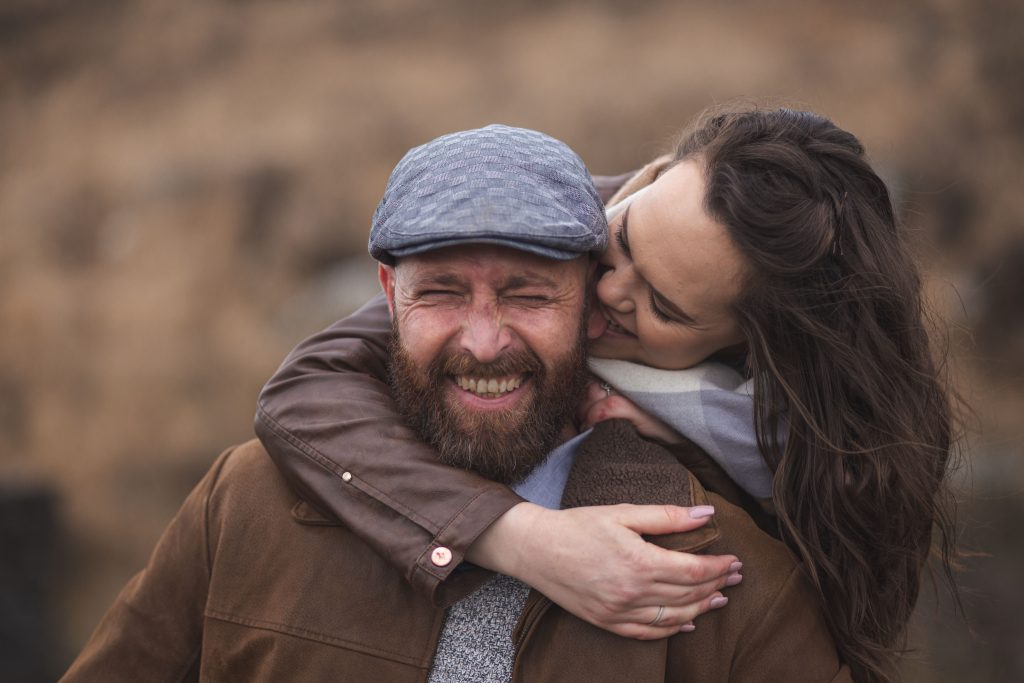 Marli + Andre wicklow mountains engagement shoot bitting his ear