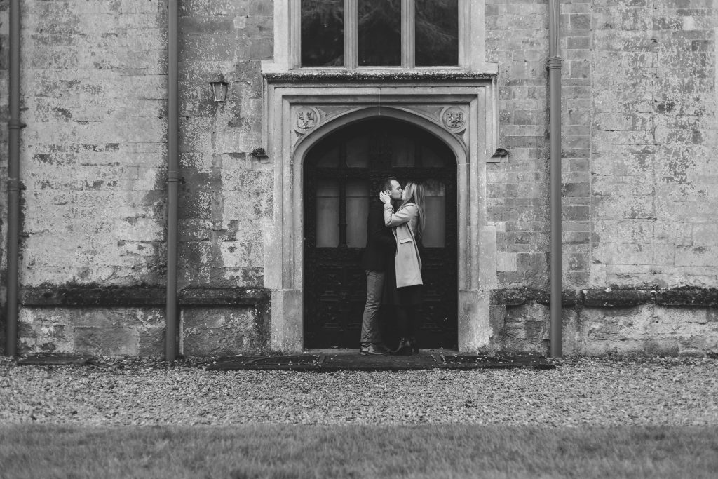 Luke and Kate kissing in a doorway at the Wroxton Abbey