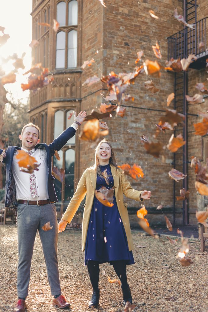 Luke and Kate throwing leaves up in the air at the Wroxton Abbey in Banbury