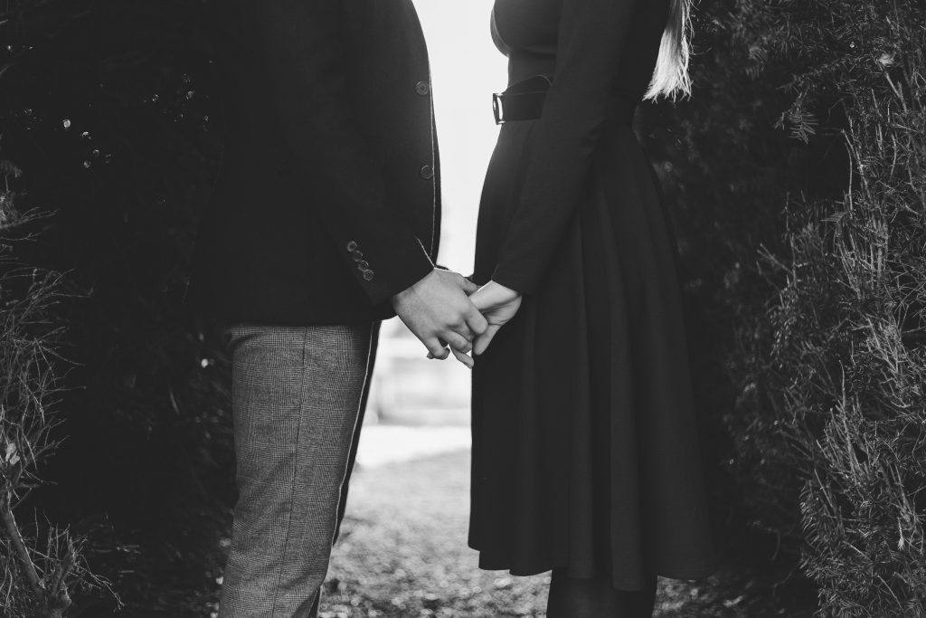 Luke and Kate couple holding hands in black and white