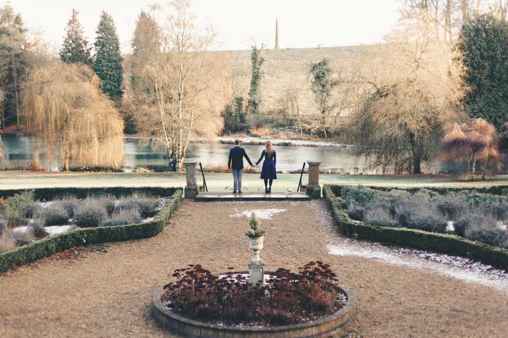 Luke and Kate holding hands infront of a lake at the Wroxton Abbey