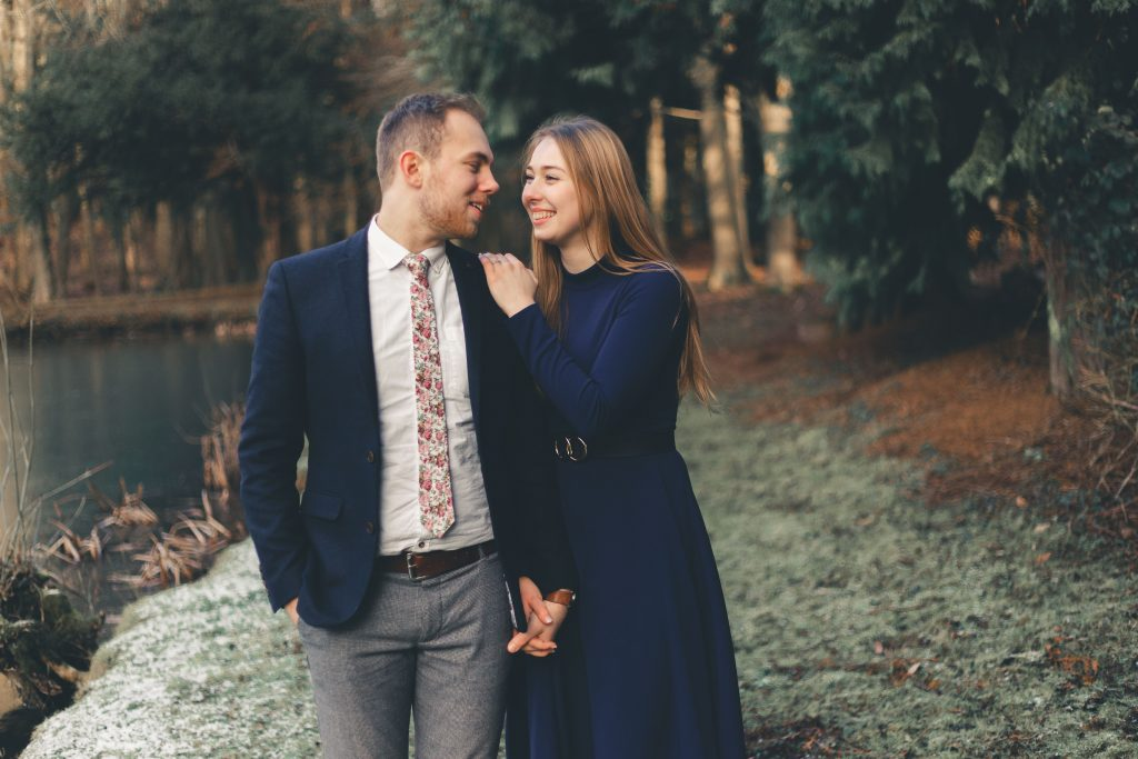 Luke and Kate engagement shoot walking next to a lake at the Wroxton Abbey in Banbury