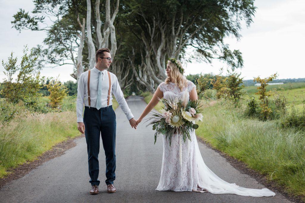 Jack and Katie Dark hedges Elopement wedding photographyJack and Katie Dark hedges Elopement wedding photography holding hands