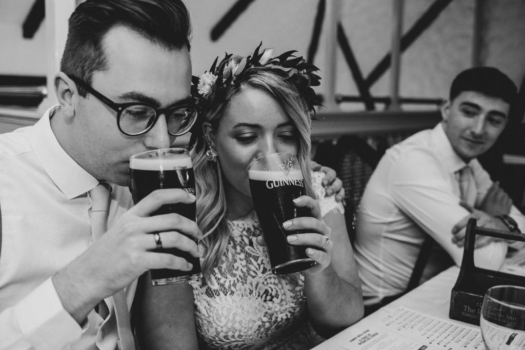 Jack and Katie the Ramble Inn Bar Restaurant Elopement wedding photography couple sharing a pint of guinness