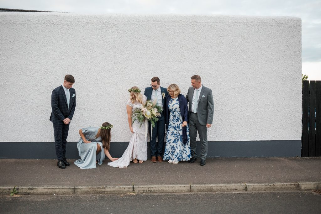 Jack and Katie the Ramble Inn Bar Restaurant Elopement wedding photography bridesmaid fixing brides dress