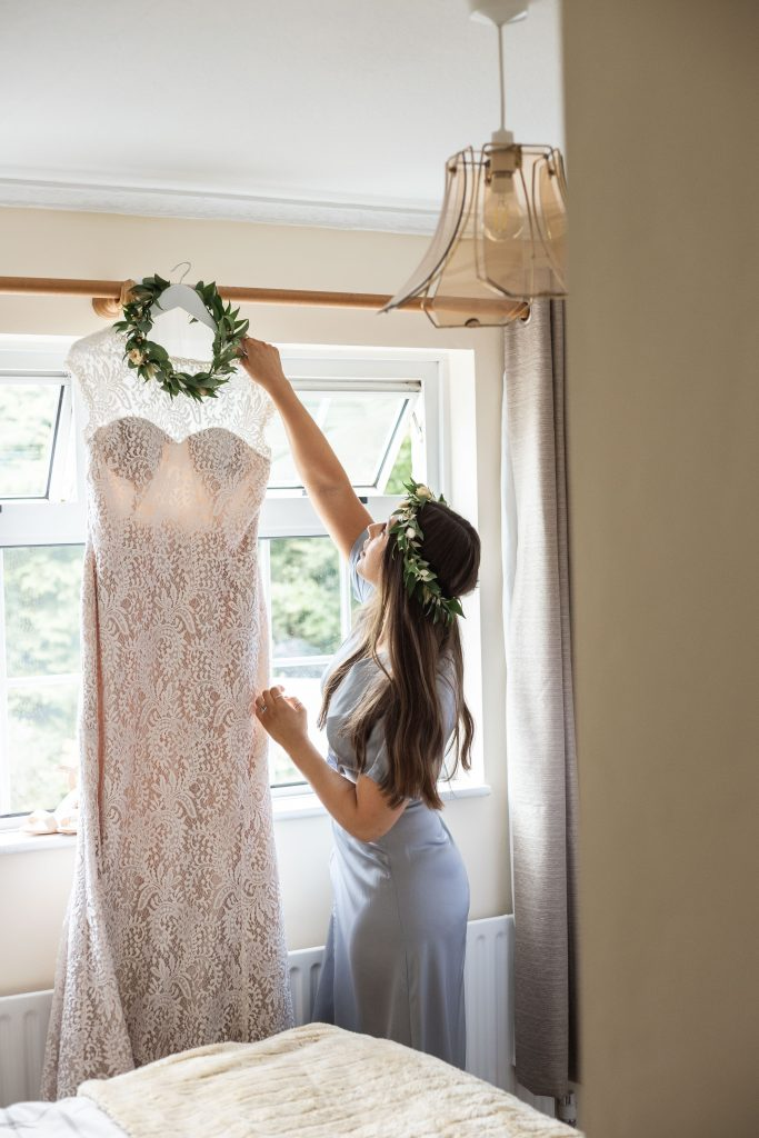 Jack and Katie Antrim elopement bridesmaid helping and hanging up wedding dress