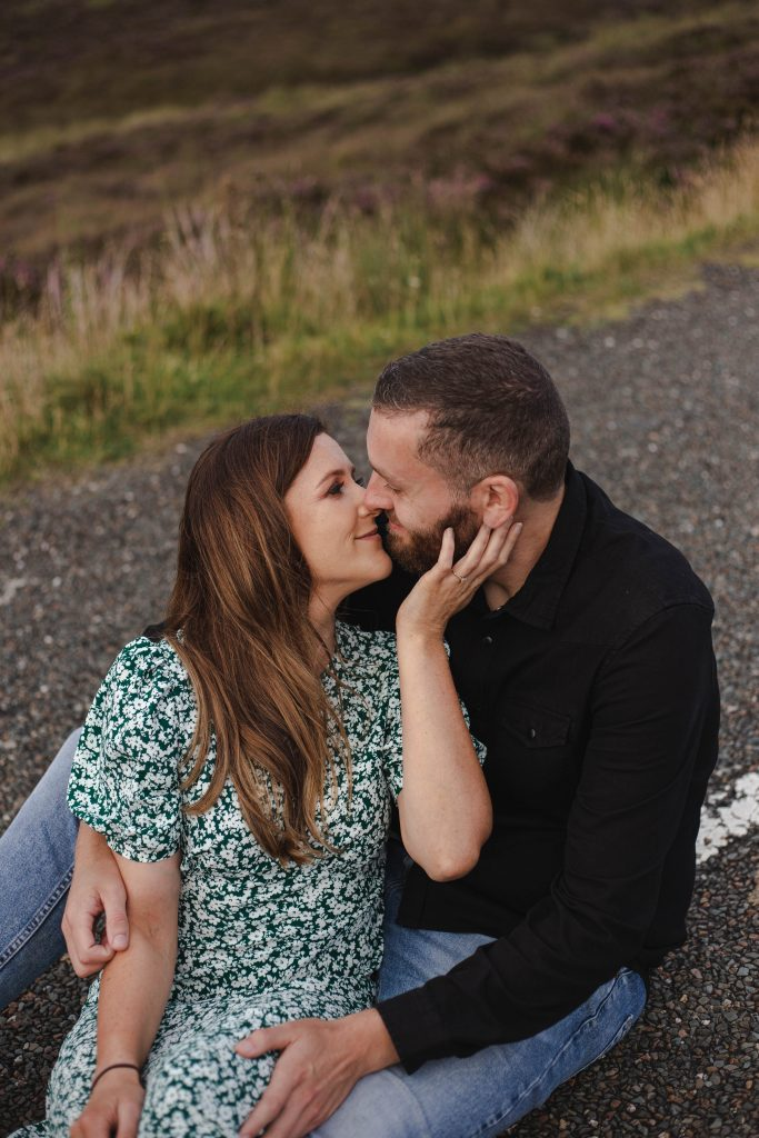 Anna and Colm engagement photography in wicklow mountains sitting in the road cuddling