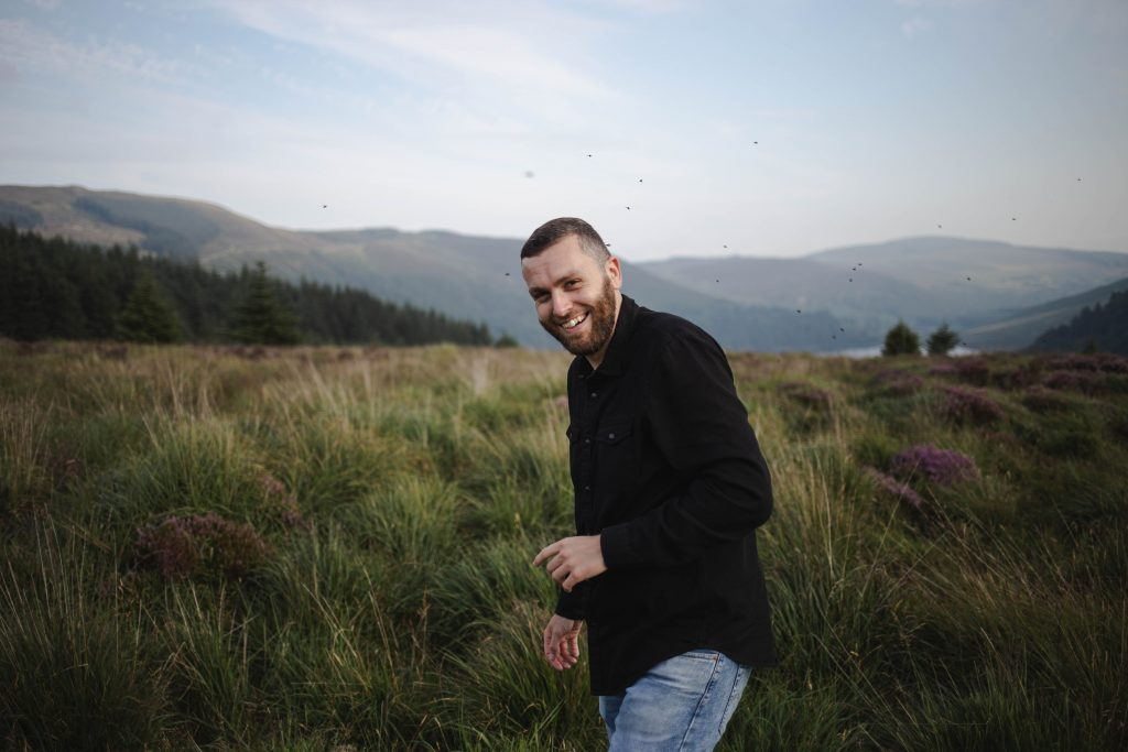 Anna and Colm couples photography in wicklow mountains man surrounded by fies