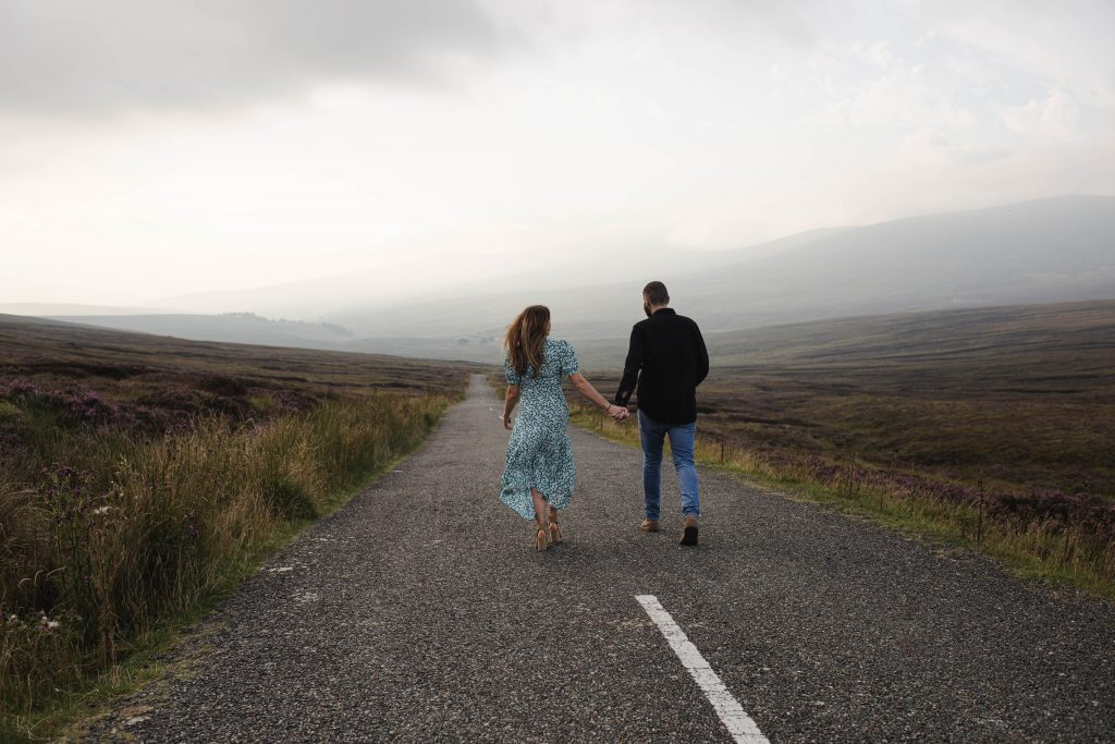 Anna and Colm couples photography in wicklow mountains walking down a road holding hands