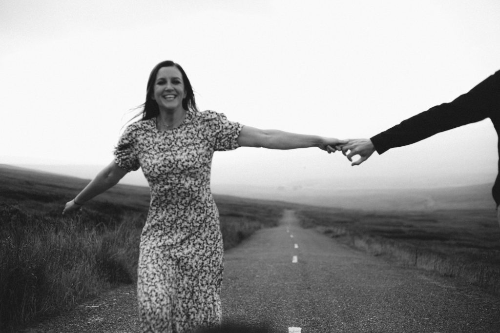 Anna and Colm couples photography in wicklow mountains running down a road holding hands