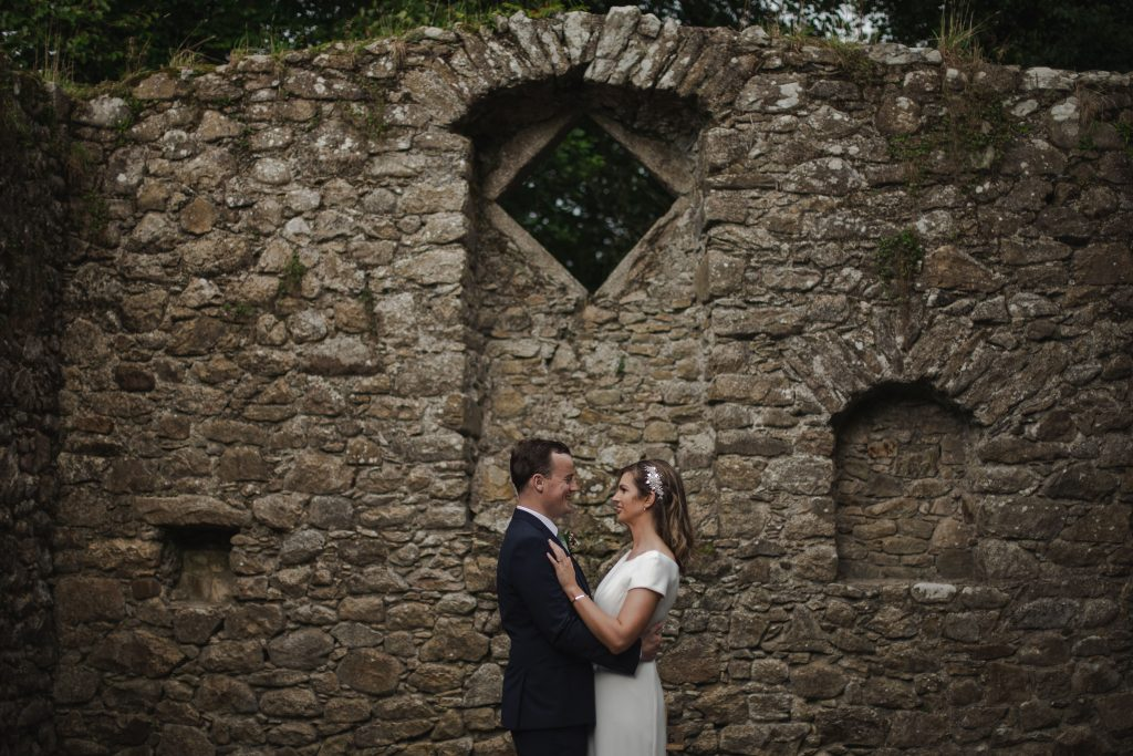 Gemma and Paddy New Ross wedding couple castle ruins with couple facing each other