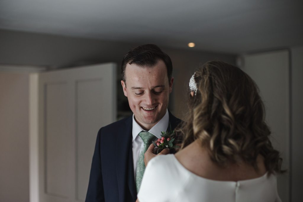 Gemma and Paddy New Ross Intimate wedding bride pinning boutonniere on groom