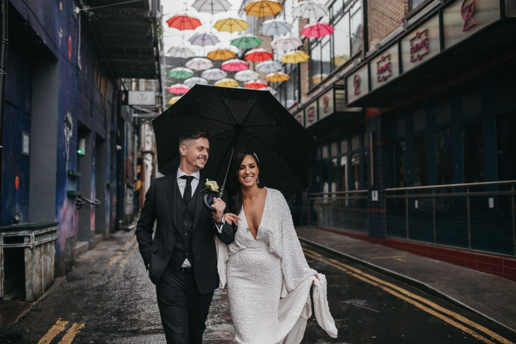 Troy and Laura Dublin City intimate Wedding under the Dublin umbrellas walking together
