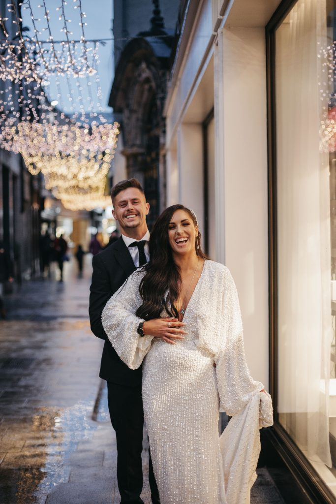 Troy and Laura Dublin City Wedding Grafton street christmas lights laughing couple