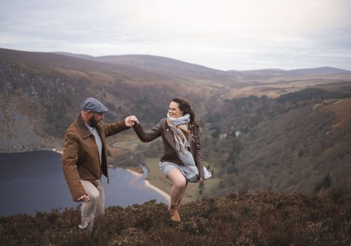 Marli + Andre wicklow mountains engagement shoot happy couple walking up a hill in the mountains